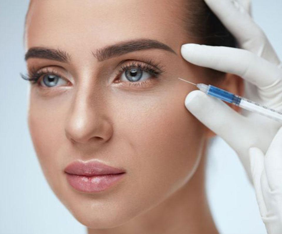 Woman getting botox injection near eye