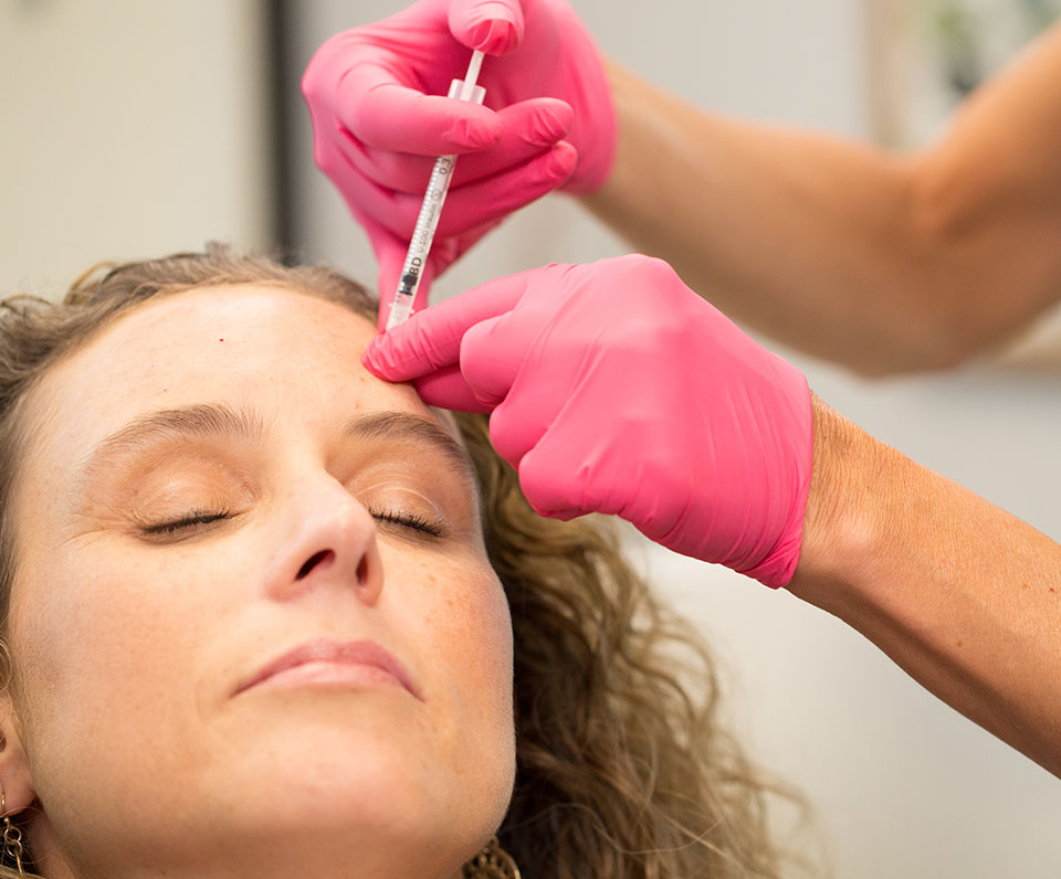 Woman getting botox injection in her forehead at Pure Aesthetics