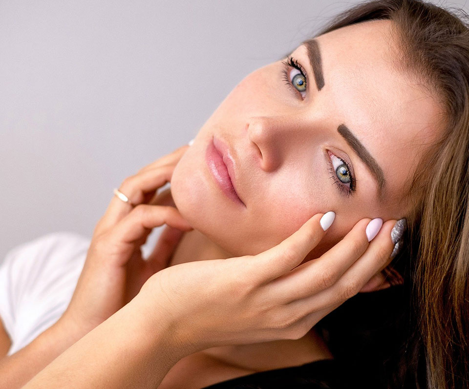 Beautiful woman staring off with hand on face